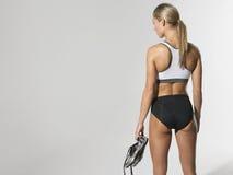 Серьезная спортсменка держа ботинки Стоковая Фотография RF