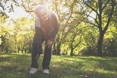 Серьезная старшая женщина имея боль в колене после тренировки стоковые фото