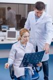 Серьезная славная женщина советуя с ее коллегой Стоковые Фотографии RF