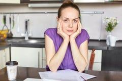 Серьезная темная с волосами молодая домохозяйка работает независимое, держит руки на щеках, работах с печатными документами, выпи стоковые изображения