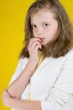 Серьезная 8-ти летняя девушка на желтой предпосылке Стоковое Фото