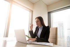 Серьезная concerned молодая коммерсантка работая на usi стола офиса Стоковое Фото