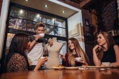 Серьезное молодые люди сидя в обсуждать чая модного кафа выпивая стоковые изображения