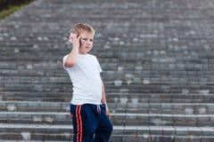 Серьезное положение мальчика на шагах и говорить по телефону outdoors стоковое изображение rf