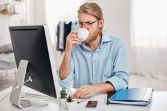 Серьезное сконцентрированное на работнике офиса работы с справедливыми волосами, бородой в вскользь обмундировании и стеклами, по Стоковые Фотографии RF