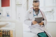 Серьезное чтение доктора от планшета стоковая фотография rf