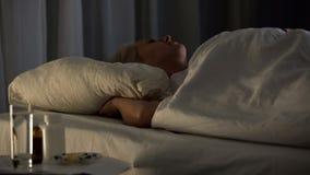 Серьезно больная больничная койка с таблицей таблеток анальгетика, заболевание спать женщины стоковое фото rf