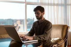 Серьезно и молодой парень битника используя портативный компьютер, надомный труд персоны Стоковые Фото