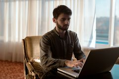 Серьезно и молодой парень битника используя портативный компьютер, надомный труд персоны Стоковое фото RF
