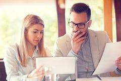 Серьезно сфокусированные предприниматели используя цифровую таблетку на кофе стоковые изображения rf
