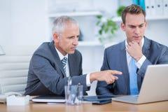 Серьезные бизнесмены работая совместно на компьтер-книжке Стоковая Фотография RF
