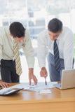 Серьезные бизнесмены работая совместно полагаться на столе Стоковые Фотографии RF