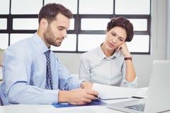 Серьезные бизнесмены работая с документами в офисе Стоковые Фотографии RF