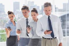 Серьезные бизнесмены стоя совместно в линии с их толпой Стоковая Фотография