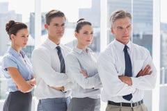 Серьезные бизнесмены стоя совместно в линии Стоковая Фотография
