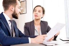 Серьезные деловые партнеры обсуждая контракт Стоковые Фотографии RF