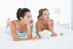 Серьезные женские друзья при шар попкорна лежа в кровати Стоковые Фото
