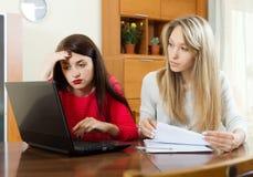 Серьезные женщины с финансовыми документами и компьтер-книжкой Стоковое Изображение
