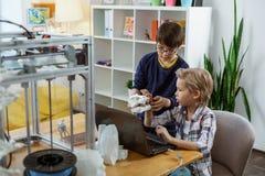 Серьезные мальчики сидя в оборудованной лаборатории с ноутбуком стоковые изображения