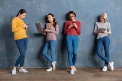 Серьезные молодые женщины полагаясь к стене стоковое изображение rf