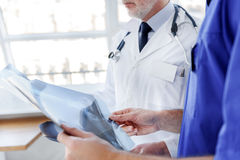 Серьезные мужские доктора анализируя изображение рентгена Стоковая Фотография