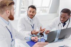 Серьезные доктора анализируя рентгенограмму на совете Стоковое Фото