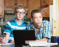 Серьезные друзья изучая в кухне Стоковая Фотография RF