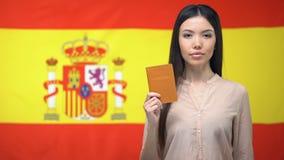 Серьезный азиатский паспорт показа женщины против испанской предпосылки флага, миграции сток-видео