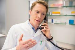 Серьезный аптекарь на телефоне стоковые фото