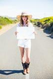 Серьезный белокурый держа знак пока путешествующ автостопом на дороге Стоковые Изображения