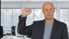 Серьезный бизнесмен веселя с кулаком вверх в современном офисе акции видеоматериалы