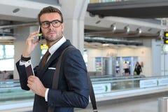 Серьезный бизнесмен во время телефонного звонка на авиапорте стоковая фотография