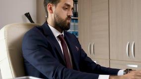 Серьезный бизнесмен в его офисе связывая его связь сток-видео