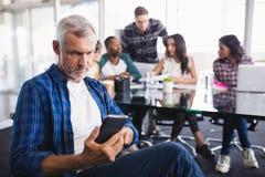 Серьезный бизнесмен используя мобильный телефон при команда работая в предпосылке Стоковые Фото