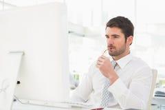Серьезный бизнесмен используя монитор компьютера стоковая фотография