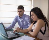 Серьезный бизнесмен и женщина смотря компьтер-книжку экранируют дома офис Стоковая Фотография RF