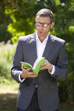 Серьезный бизнесмен наслаждаясь читающ книгу в идти снаружи Стоковые Изображения RF