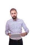 Серьезный бизнесмен показывая таблетку цифров над белой предпосылкой стоковая фотография rf