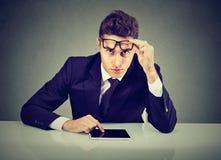 Серьезный бизнесмен при компьютер пусковой площадки смотря камеру стоковые изображения rf