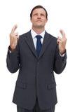 Серьезный бизнесмен при пересеченные перста смотрит вверх Стоковые Изображения
