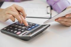 Серьезный бизнесмен работая на смотреть документов сконцентрировал с портфелем и телефоном на таблице Стоковые Фото
