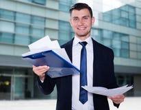 Серьезный бизнесмен рассматривает документы перед подписанием Стоковое Изображение RF