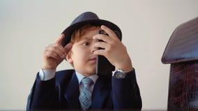 Серьезный бизнесмен ребенка просматривает мобильный телефон сток-видео