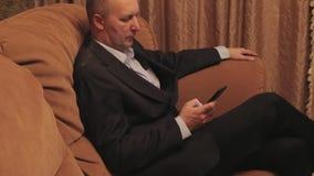 Серьезный бизнесмен смотря информацию в smartphone сидя на софе видеоматериал