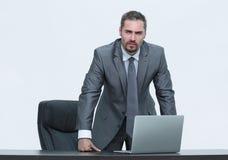Серьезный бизнесмен стоя за столом Изолировано на белизне стоковые фотографии rf