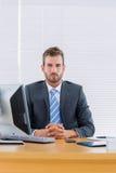 Серьезный бизнесмен с компьютером на столе офиса Стоковые Изображения