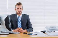 Серьезный бизнесмен с компьютером на столе офиса Стоковая Фотография RF