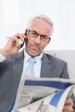 Серьезный бизнесмен с мобильным телефоном и газетой дома Стоковая Фотография