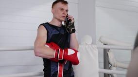 Серьезный боец человека говорит на смартфоне во время перерыва тренировки на ringside акции видеоматериалы