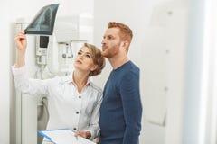 Серьезный женский врач в шкафе с прибором рентгеновского снимка Стоковая Фотография RF